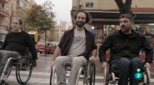 Tres jóvenes cruzan un paso de cebra en sillas de ruedas