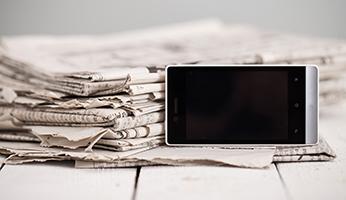 periódicos y móvil en una mesa