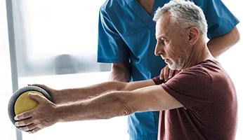 Hombre mayor haciendo rehabilitación de brazos