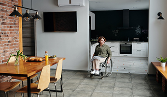 mujer en silla de ruedas en el interior de una vivienda