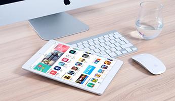 Tableta con aplicaciones en mesa de ordenador